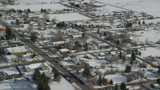 AX126_210 - 6K stock footage aerial video of flying over snowy small town neighborhoods in winter, Midway, Utah