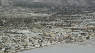 AX126_216 - 6K stock footage aerial video orbit tract homes by snowy field on outskirts of Heber City in winter, Utah