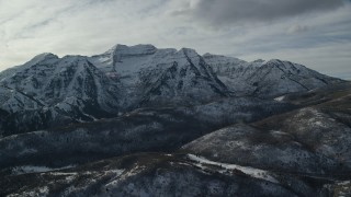 AX126_238 - 6K stock footage aerial video orbit tall, rugged Mount Timpanogos with winter snow in the Wasatch Range, Utah