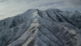 AX126_244 - 6K stock footage aerial video orbit of rugged Mount Timpanogos with winter snow in Utah