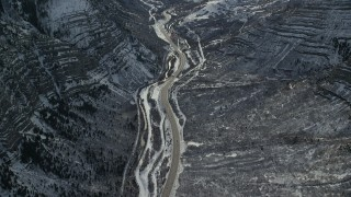 AX126_248 - 6K stock footage aerial video of bird's eye of Provo Canyon Road through the snowy Wasatch Range in winter, Utah