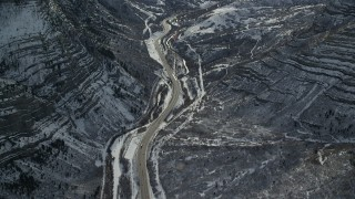 AX126_249 - 6K stock footage aerial video bird's eye of Provo Canyon Road winding through snowy mountains in Utah