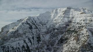 AX126_250 - 6K stock footage aerial video orbit snowy, rugged slopes of Mount Timpanogos in winter, Utah