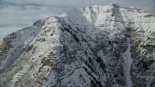 AX126_251 - 6K stock footage aerial video flyby steep, snowy slopes of Mount Timpanogos in winter, Utah