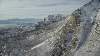 AX126_252 - 6K stock footage aerial video orbit rocky slopes of Mount Timpanogos with winter snow in Utah