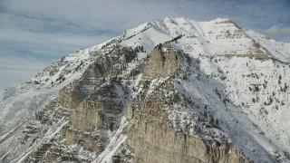 AX126_254 - 6K stock footage aerial video orbit steep slopes of snowy Mount Timpanogos in winter, Utah
