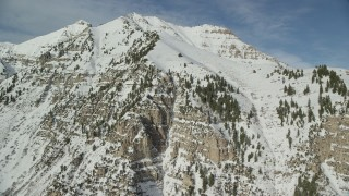 AX126_256 - 6K stock footage aerial video orbit steep and snowy slopes of Mount Timpanogos near the summit in winter, Utah