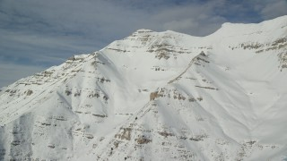 AX126_260 - 6K stock footage aerial video of Mount Timpanogos slopes covered in winter snow in Utah