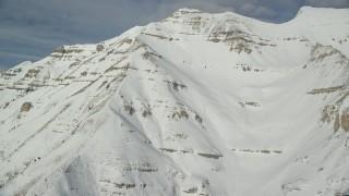 AX126_261 - 6K stock footage aerial video orbit around steep, snowy slopes of Mount Timpanogos in Utah