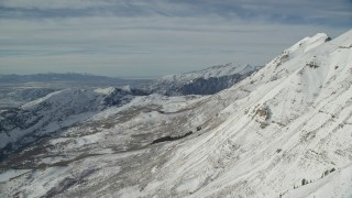 AX126_263 - 6K stock footage aerial video fly over frozen Mount Timpanogos slopes in wintertime, Utah