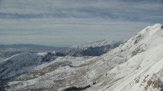 AX126_264 - 6K stock footage aerial video fly over steep, snow covered Mount Timpanogos slopes in Utah