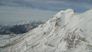 AX126_266 - 6K stock footage aerial video approach the north end of snowy Mount Timpanogos in winter, Utah