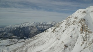 AX126_267 - 6K stock footage aerial video of Wasatch Range snow mountains and the north end of Mount Timpanogos in Utah