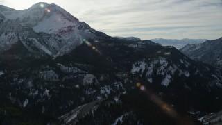 AX126_282 - 6K stock footage aerial video orbit north side of Mount Timpanogos with wintertime snow, Utah