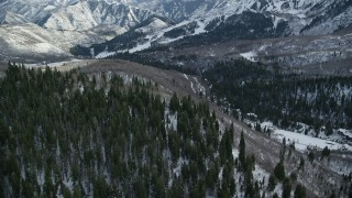 AX126_294 - 6K stock footage video fly over evergreens to approach Sundance Mountain Resort in winter, Utah
