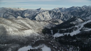 AX126_297 - 6K stock footage aerial video fly over Sundance to approach mountains with light winter snow, Utah