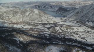AX126_301 - 6K stock footage aerial video approach Deer Creek Reservoir beyond a snowy valley in winter, Utah