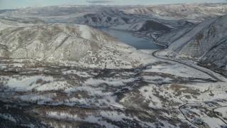AX126_302 - 6K stock footage aerial video fly over snowy valley to approach Deer Creek Reservoir in winter, Utah