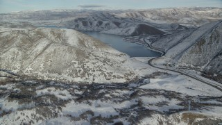 AX126_303 - 6K stock footage aerial video approach Deer Creek Reservoir from a snowy, hilly valley in winter, Utah
