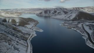 AX126_307 - 6K stock footage aerial video fly over Deer Creek Reservoir toward Heber City on the distant snowy shore, Utah