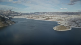 AX126_315 - 6K stock footage aerial video approach Heber City from icy patches in the Deer Creek Reservoir in winter, Utah