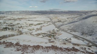 AX126_318 - 6K stock footage aerial video fly over homes in Heber City with winter snow near the highway, Utah