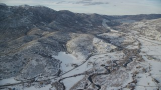 AX127_007 - 6K stock footage aerial video approach riverside rural homes and mountains with light snow near Midway, Utah