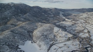 AX127_008 - 6K stock footage aerial video fly over rural homes and approach mountains with light snow in Utah