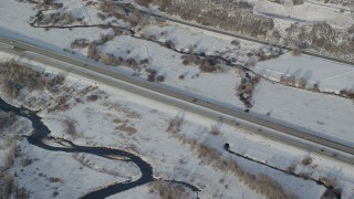 AX127_010 - 6K stock footage aerial video of tracking white car and black truck on country highway with winter snow, Heber City, Utah