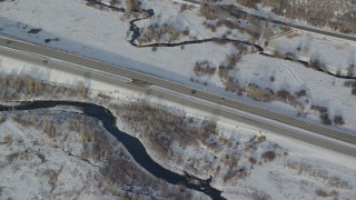 AX127_011 - 6K stock footage aerial video of tacking two cars on a highway through snowy fields in wintertime, Heber City, Utah