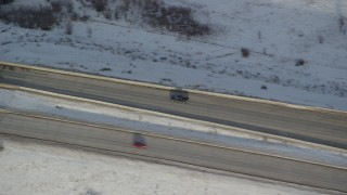 AX127_012 - 6K stock footage aerial video of tracking a black truck on a county highway and crossing a small bridge in winter, Heber City, Utah