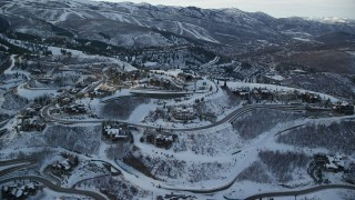 AX127_019 - 6K stock footage aerial video orbit Deer Valley mansions on a mountaintop with light snow in winter at sunset, Utah