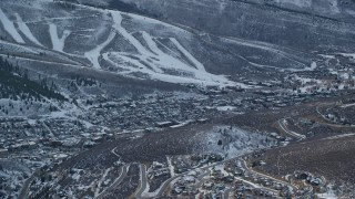 AX127_021 - 6K stock footage aerial video of orbiting Park City in the shadow of a snowy mountain at sunset, Utah