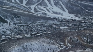 AX127_022 - 6K stock footage aerial video of passing by the center of town in Park City with winter snow on the ground at sunset, Utah