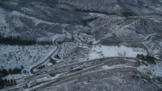 AX127_036 - 6K stock footage aerial video approach and tilt to tracks at Utah Olympic Park with winter snow at sunset, Utah