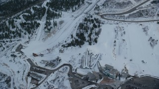 AX127_038 - 6K stock footage aerial video reverse view of the aerials pool and ski jumps at Utah Olympic Park with winter snow at sunset, Utah