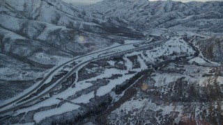 AX127_051 - 6K stock footage aerial video approach I-80 through a frozen mountain pass in winter at sunset, Utah