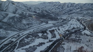 AX127_052 - 6K stock footage aerial video approach I-80 through the Wasatch Range with winter snow at sunset, Utah