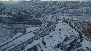 AX127_053 - 6K stock footage aerial video approach I-80 with light traffic through a wintery Wasatch Range pass at sunset, Utah