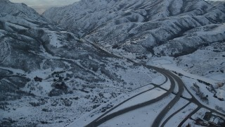 AX127_056 - 6K stock footage aerial video follow I-80 through Wasatch Range with winter snow at sunset, Utah