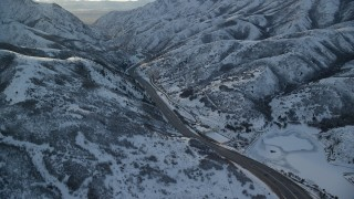 AX127_057 - 6K stock footage aerial video approach I-80 through a snowy mountain pass in wintertime at sunset, Wasatch Range, Utah