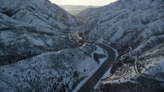 AX127_061 - 6K stock footage aerial video fly over a curve in wintery Wasatch Range mountain pass at sunset, Utah