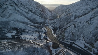 AX127_062 - 6K stock footage aerial video approach I-80 through frigid Wasatch Range pass in wintertime at sunset, Utah