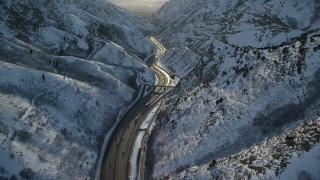 AX127_066 - 6K stock footage aerial video of freeway in the Wasatch Range with winter snow at sunset, Utah