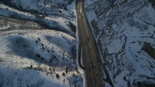 AX127_069 - 6K stock footage aerial video of a big rig and cars traveling the snowy mountain pass at sunset, Wasatch Range, Utah