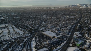 AX127_076 - 6K stock footage aerial video approach Downtown Salt Lake City from suburbs at sunset in wintertime, Utah