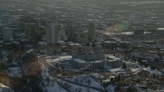 AX127_090 - 6K stock footage aerial video orbit Utah State Capitol and downtown with winter snow at sunset, Salt Lake City