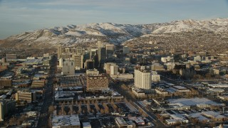 AX127_110 - 6K stock footage aerial video of buildings with winter snow in Downtown Salt Lake City at sunset, Utah