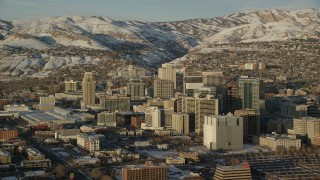 AX127_111 - 6K stock footage aerial video orbit of Downtown Salt Lake City and Utah State Capitol with winter snow at sunset