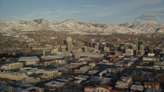 AX127_114 - 6K stock footage aerial video wide orbit of downtown area of Salt Lake City at sunset with winter snow, Utah